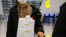 Ewakuowana z przewieszonym na szyi formularzem medycznym w kolejce na badanie lekarskie (PAP/Arek Rataj)